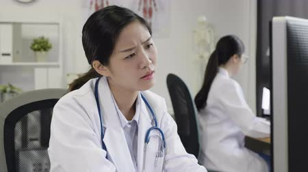 talep : slow motion confused woman doctor sitting and using computer looking screen and document on desk frowning not understanding. colleague concentrated working in background in hospital office.