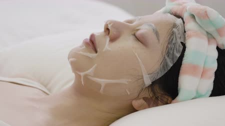 obličejový : side view asian elegant woman applying facial mask on face close eyes relaxing resting lying on white bed waiting for minutes time. girl with headband and moisturizer product sleep peaceful bedroom