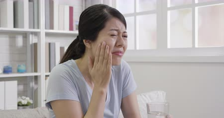 hassaslık : slow movement of young asian girl with toothache and dental problems. woman feeling pain when drinking cold water sitting sofa in apartment. lady having sensitive teeth.
