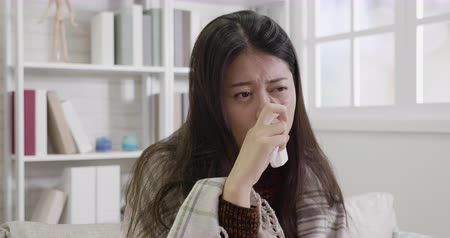 handkerchief : slow motion of flu cold sneezing woman sick blowing nose. young asian girl using hand holding tissue finger touching face. lady got nose allergy at home resting on sofa.