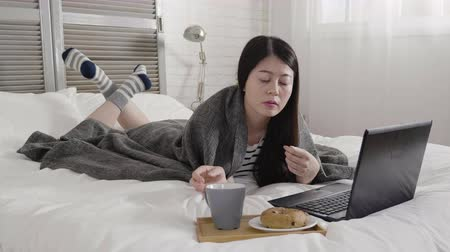 ベーグル : technology holidays christmas interior winter concept. young asian woman in cozy bedroom with laptop computer coffee cup and bagel lying on bed at home. beautiful lady typing on keyboard reply email 動画素材