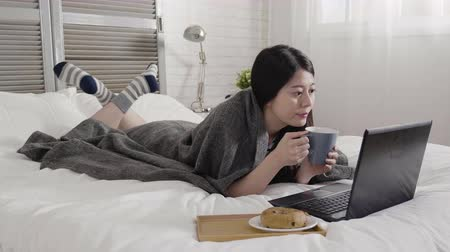 bécsi kifli : slow motion asian woman cover by warm blanket lying on front on white bed typing keyboard laptop computer with breakfast. girl drinking hot latte coffee in bedroom with tasty bagel in winter morning Stock mozgókép