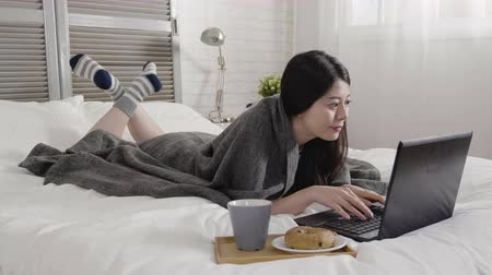 bécsi kifli : slow motion of beautiful asian female lying in bed with laptop computer typing look at notebook screen. young girl having breakfast with hot chocolate milk and delicious bagel bread relax in bedroom