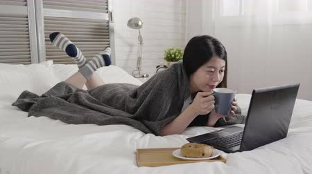 bécsi kifli : lady freelancer lying on bed in hotel room by window and working in laptop computer. woman having breakfast in bedroom with hot cocoa and delicious bread. girl cover by blanket in winter morning