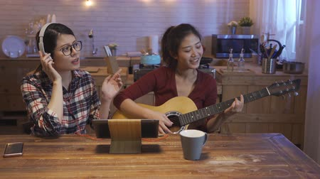 居心地のよい : Group of female friends singing music while wearing headphones and playing guitar in warm modern cozy kitchen at home at night. happy girls love songs together happily with digital pad on wood table
