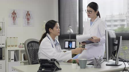 talep : asian female medical team discussing over desktop computer monitor in working office at hospital. young woman coworker sitting on desk relying holding document pointing on screen while talking.