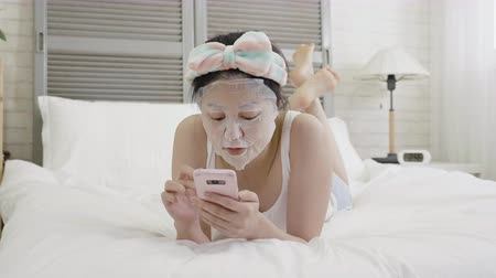 headband : slow motion young asian girl applying facial mask pure on face using mobile phone browsing website online.