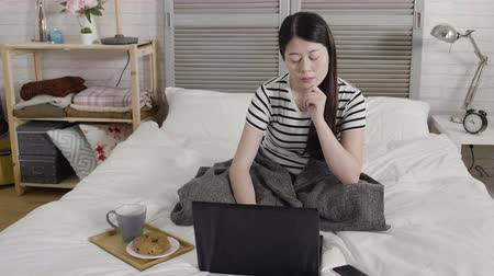 bécsi kifli : slow motion elegant woman thinking sit in bed with notebook computer typing working in cold winter morning cover body by warm blanket. young lazy girl having breakfast with hot cup cocoa and bread Stock mozgókép