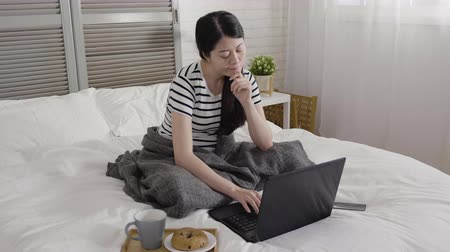 bécsi kifli : slow motion pretty young college student working at home doing project on laptop computer sitting in bed staring thoughtfully into air in winter morning. asian female having breakfast coffee bagel Stock mozgókép