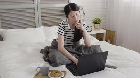 bécsi kifli : thoughtful asian female freelancer working at home in cold winter morning sitting in bed typing on keyboard laptop computer. young girl worker sick replying emails in bedroom with breakfast near by.