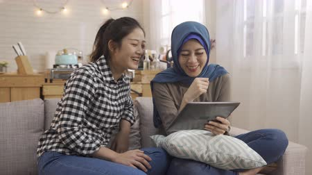 ислам : happy young asian college girl with classmate female muslim student smiling looking digital pad together. women friends sitting on couch sofa at home laughing having fun watching video on tablet. Стоковые видеозаписи