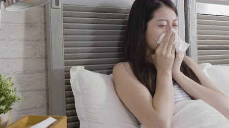 alerji : Sick asian girl sitting on bed sneezing in handkerchief and tissue box on table beside her in cozy white bedroom.
