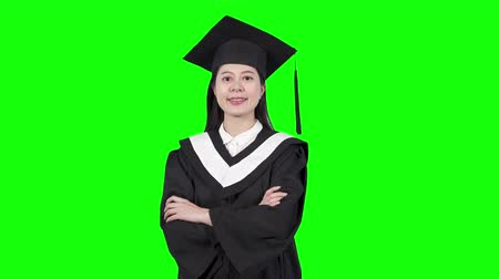 promoce : Young pretty chinese girl smiles happily into camera close up over green chroma key screen background. successful college student in graduate gown and cap standing crossed arms. confident asia female