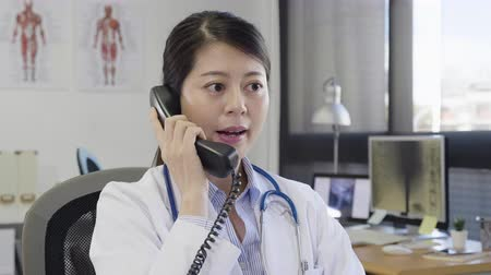 korejština : slow motion medical nurse doctor answer talking on telephone wearing white lab coat and stethoscope smiling friendly. female worker in hospital pick up phone discussing with patient in clinic office
