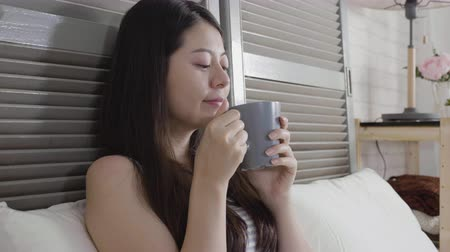 yorgan : Cheerful woman drinking morning coffee lying in bed. young girl cover body under white quilt wearing tank top having hot cocoa in cold winter. relaxed female in bedroom laughing smiling feels better. Stok Video