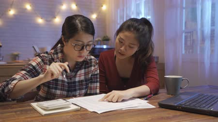 点数 : Asian female at kitchen table frowning accounting on calculator. Savings finances and economy concept. woman roommate friend give cup of water found mistake on paper telling girl count again.