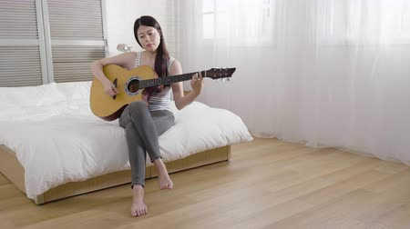 guitarrista : relaxed talented female musician create new song and playing modern acoustic guitar in bedroom in the morning.