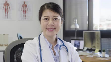 korejština : Portrait of asian doctor woman with stethoscope sitting at working desk in modern hospital office.