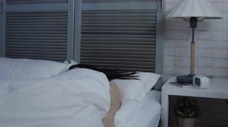 minder : slow motion young beautiful asian woman with insomnia cant sleep at night in dark cozy bedroom. Stok Video