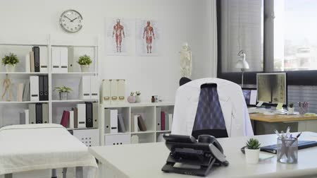 интерьер : Empty nobody doctor office with white lab coat on chair in the morning in clinic. Стоковые видеозаписи