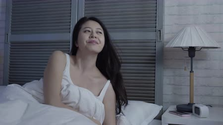 bezsennosć : slow motion asian woman wakes up in the middle of night in frustration unable to sleep.