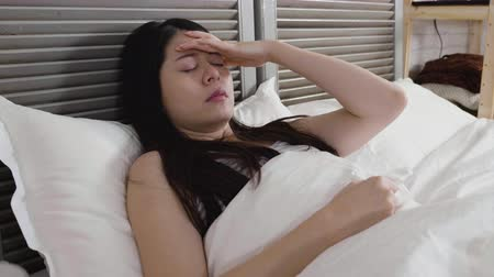 zsebkendő : slow motion ill asian woman with handkerchief. Sick girl has runny nose sleeping resting on bed full of tissue around. lady patient makes a cure for common cold having high temperature fever headache