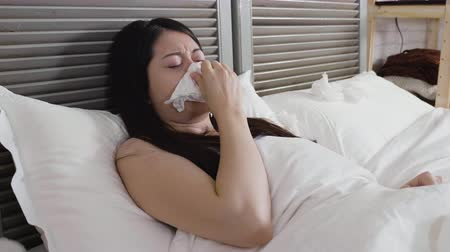 pokrývka hlavy : slow motion sick asian woman in flu caught cold sneezing into tissue. ill female blowing runny nose in handkerchief lying in bed resting at home. Sick woman with headache cover under blanket. Dostupné videozáznamy