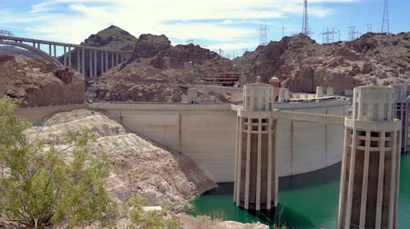 водохранилище : left to right view Hoover Dam Lake Mead producing hydroelectricity above Colorado River Bridge on US 93 Las Vegas Nevada Arizona USA. cars driving on highway road sunny day with blue sky