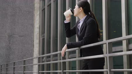 superior : Corporate time out. slow motion side portrait of young smiling office lady standing on balcony with cup of coffee out of office in skyscraper building. successful business woman drinking on sunny day