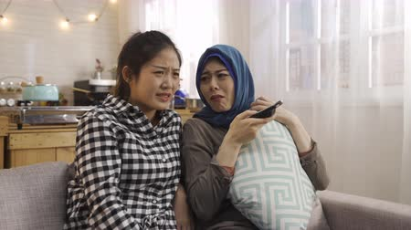pokrývka hlavy : arabic ethnic woman with religion scarf cover head sitting on couch relax in leisure time with asian college classmate girl student in dormitory kitchen. scared friends watch horror movie on tv chat