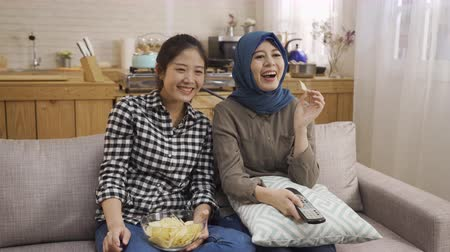 контроллер : happy multi female best friends sit on couch watch funny film on TV. group of asian arabic women eating snacks laughing talking with comedy program on television holding controller at home kitchen