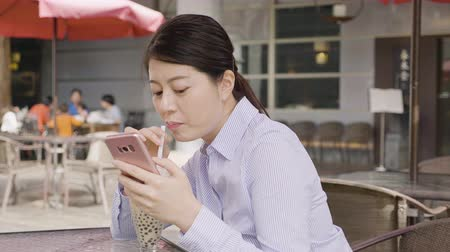 tapioca : young elegant businesswoman sitting having afternoon tea drinking ice milk tea with bubble in glass on table in outdoor cafe in city taipei taiwan. office lady relax using cellphone in lunch time. Stock Footage