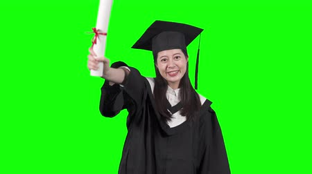 korejština : happy beautiful young asian female graduate in traditional clothes and cap smiling to camera and holding her diploma on green background.