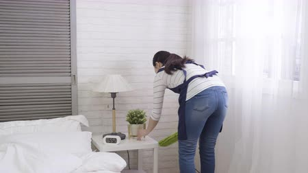 korejština : slow motion young female japanese housekeeper cleaning nightstand in hotel room.