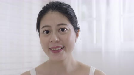 чувствовать : beauty skin care and people concept. slow movement happy young chinese woman applying cream to face and looking to mirror at home in cozy comfort bedroom.