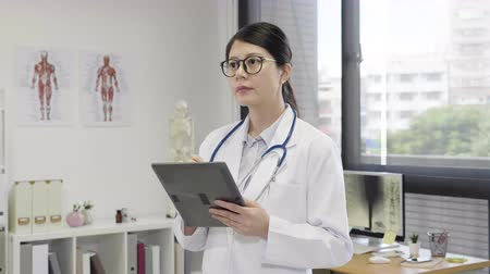 pedleri : slow motion of thoughtful woman doctor thinking while using digital pad standing in modern clinic office. Stok Video