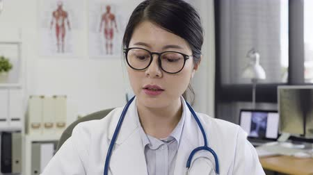 prescribe : Friendly female asian doctor in white lab holding blister of medicine explaining to patient in modern office clinic. Stock Footage