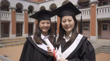 korejština : closeup beautiful smile chinese graduate graduated student girl young women in cap gown holding diploma scroll.