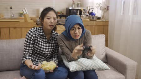 korejština : Two female teenagers asian and islam female playing video games on tv holding joystick.