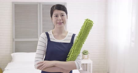 dienstbode : slow motion of young elegant asian beautiful housewife wear blue apron looking at camera with attractive smiling face. Stockvideo