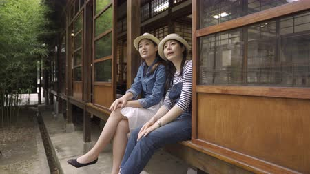 kyoto : two young asian female friends talking and showing something pointing sky while sitting in wooden japanese style house.