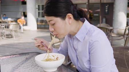 ramen : slow motion of asian woman sucking spaghetti by chopsticks in outdoor cafe restaurant in italy.