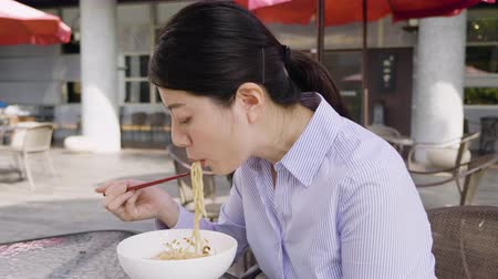 sucking : slow motion asian business woman eating noodle on lunch break outdoor cafe restaurant.