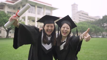 promoce : slow motion of two asian college girl students hugging together standing outdoor on grass meadow with thumb up gesture. Dostupné videozáznamy