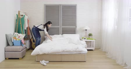 housekeeper : busy housewife cleaning bedroom making bed white sheet putting shoes in right place on shelf.