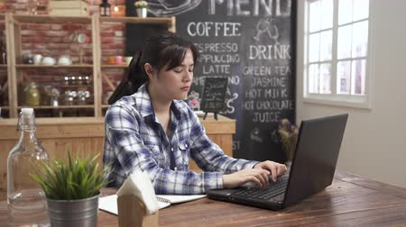 kahvehane : Young asian japanese woman sitting in coffee shop at wooden table using laptop. Stok Video