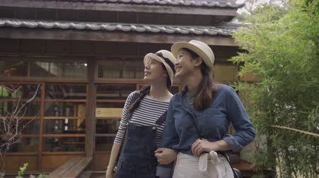 osaka : two young carefree woman tourists pointing and talking with amazing view in peaceful japanese style garden by traditional wooden house in kyoto japan. girls travelers arms in arms standing outdoor. Stock Footage
