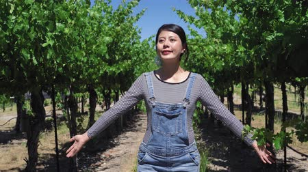éretlen : happy young asian woman farmer relax smiling cheerful walking by unripe green grapes in vineyard on sunny day. female winemaker in owner farm satisfied with her fruits plants open arms early summer