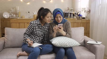 malaya : happy relax multi female friendship at home. malay woman talking telling news on smart phone sharing with korean girl who hard working doing homework on couch. two asian ladies discuss on cellphone Stok Video