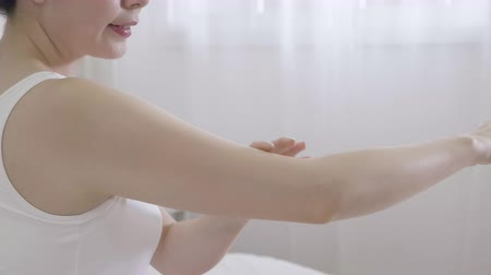 чувствительный : Happy asian woman looking at hands shoulders arms while applying cream. young girl cheerful touching finger jumping enjoy perfect body skin. elegant female in cozy white bedroom apartment home. Стоковые видеозаписи